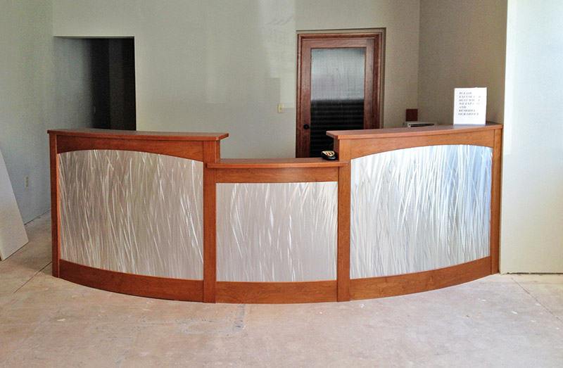A new curved reception desk for Northland EyeCare of Flagstaff Az.  The desk features a curved design, brushed stainless laminate and cherry stained wood.