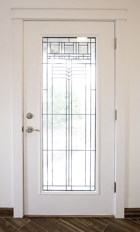 Interior side of a custom front door with full glass and craftsman trim