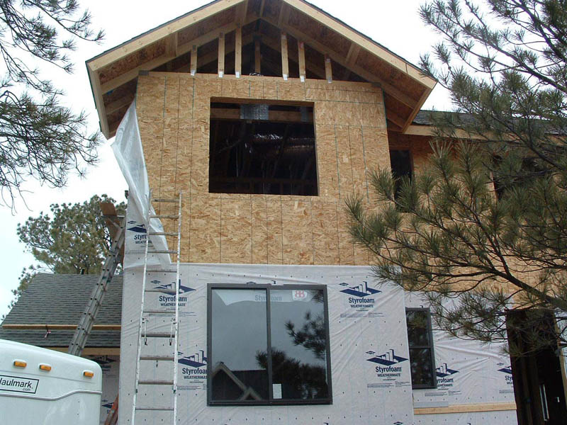 Installing house wrap in preparation for siding