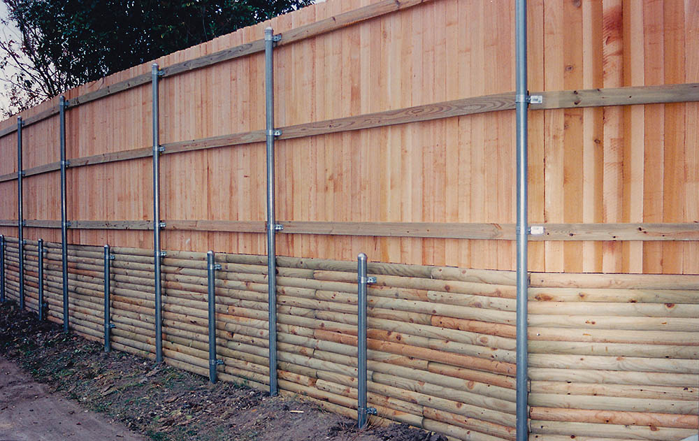 Custom fence with a treated lumber retaining wall and metal posts