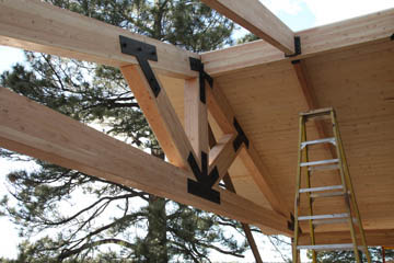 Custom carpentry of lodge style beams with custom steel brackets over deck in Flagstaff Arizona